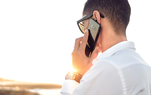 A man holds a smartphone up to his ear