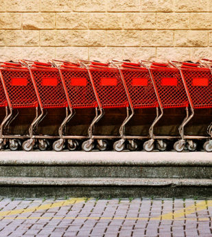 Shopping carts lined up on a brick wall