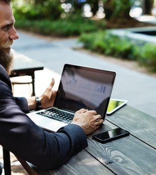 Man looking at laptop with graph on screen
