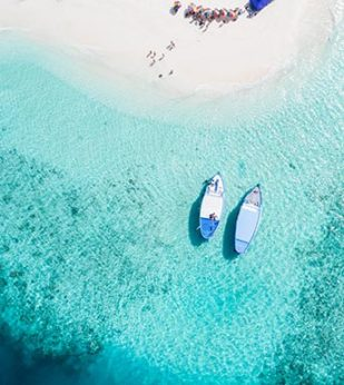 two boats anchored near crystal blue water