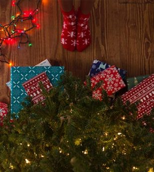 Wrapped gifts under a Christmas Tree with person wearing socks nearby