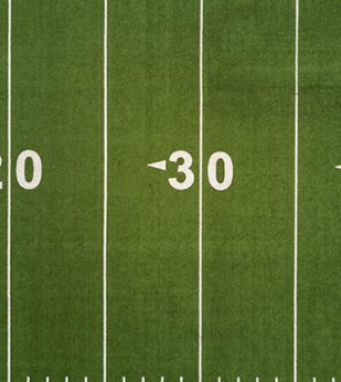 Aerial view of an American football field, showing the 20 and 30 yard lines.