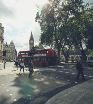 London street with a red tour bus in the foreground and Big Ben in the background