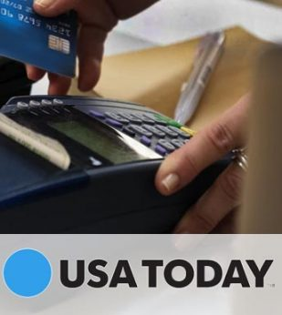 A woman slides a blue credit card through a card reader on a desk. The USA Today logo is below the image.