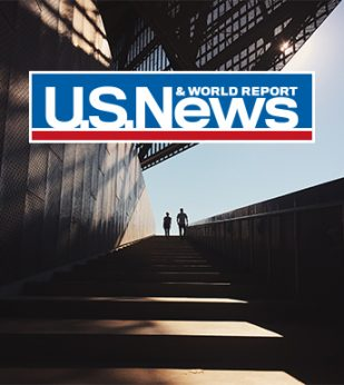 People standing near building with US News logo overlayed