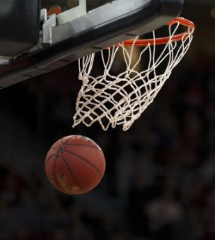 A basketball goes through a hoop on a darkened stadium.