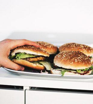 person grabbing hamburger off tray of burgers