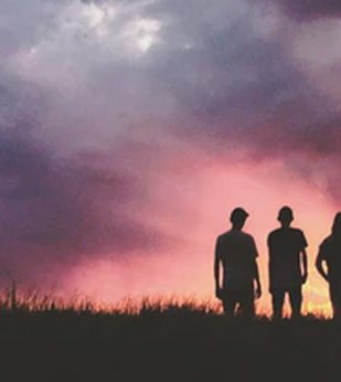 people standing in a field at sunset