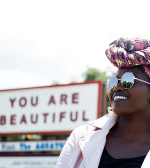 a woman stands in front of a sign that says 'you are beautiful'