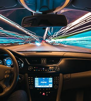 A long exposure view looking out a car windshield going through a tunnel