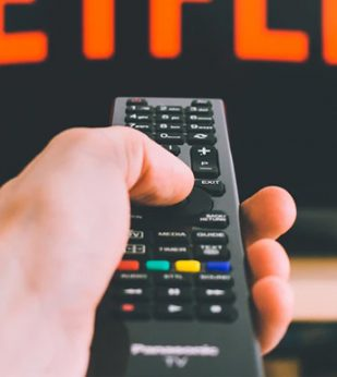 Person points remote at TV