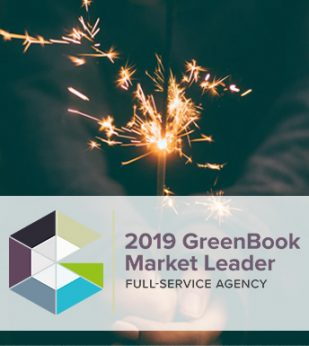 A woman holds a sparkler against a dark background. The GreenBook Market Leader logo is below.