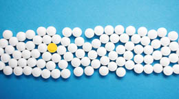 White tablet pills on a blue background with one differentiating yellow pill