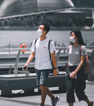 Two people wearing masks walk along a river