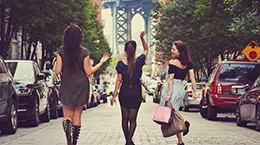 Women happily walk down the street carrying shopping bags