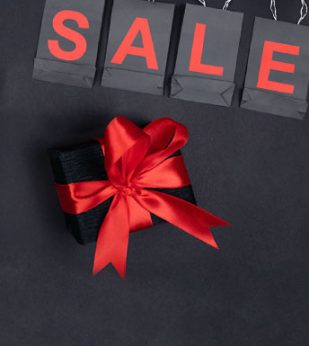 Gifts wrapped in black paper and red bows sit on a dark background.