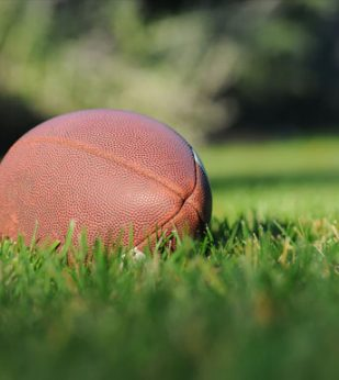 A football sits in a field of grass