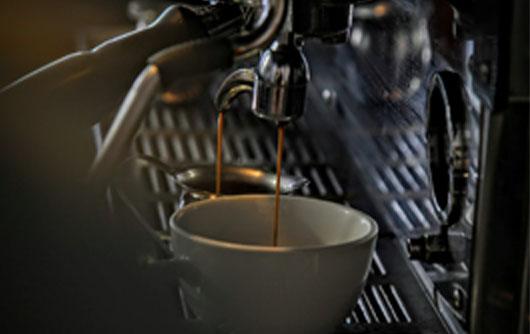 Espresso dispenses into a mug