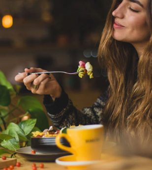 A woman sits at a table and brings a forkful of food to her mouth