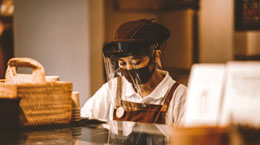 A restaurant worker preps food in a mask and face shield