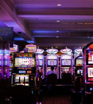 A man sits alone at a slot machine in a casino
