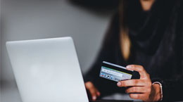 A person holds up a credit card while on a laptop