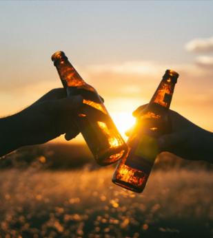 People cheers beer bottles against a sunset