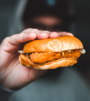 A person holds a chicken sandwich